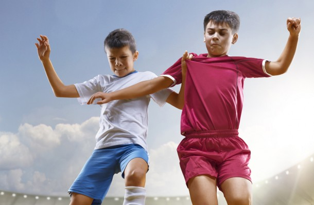 Childrens are playing soccer on grand arena in sunlights
