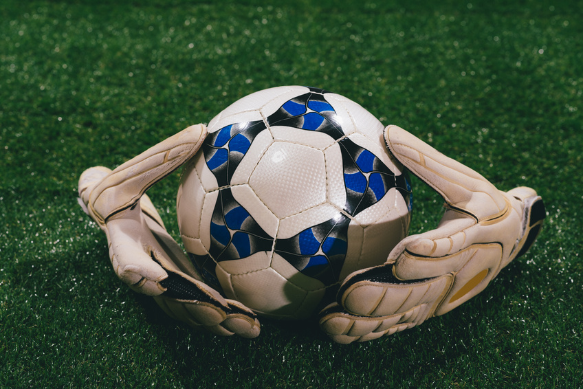 Soccer ball and goalkeeper gloves on the field